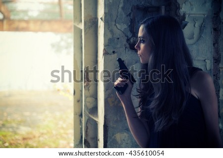 Woman with a gun waiting behind the corner