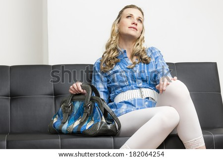 woman with a handbag sitting on sofa