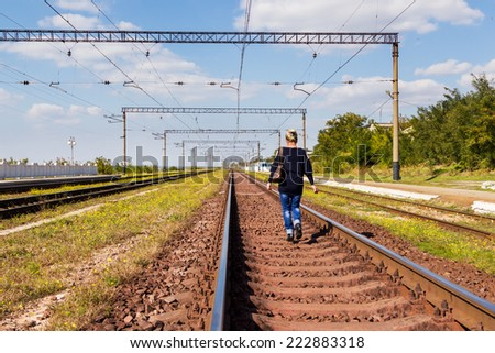 Woman with a handbag walking on railroad tracks away from the camera - stock photo