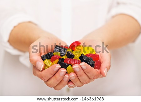 Woman with a handful of multicolored candies - stock photo