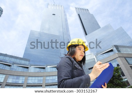 Woman with a hardhat writing on a clipboard while standing in front of a skyscraper.