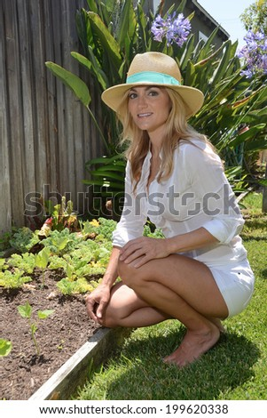 Woman with a hat in a garden environment/Woman In Garden/Woman enjoys working in her garden on a summer day
