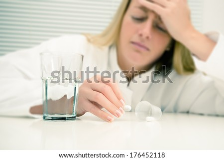 Woman with a headache, shallow DOF, toned image, focus on the hand holding a pill