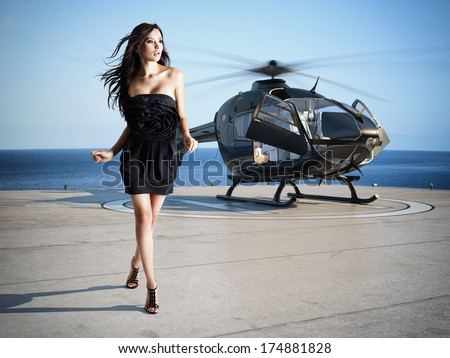 woman with a helicopter in the background - stock photo
