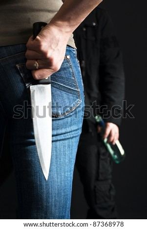 Woman with a knife facing her drunk husband. - stock photo
