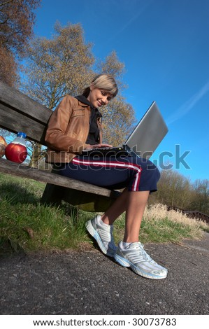 Woman with a laptop computer sitting outdoors on a bench. - stock photo