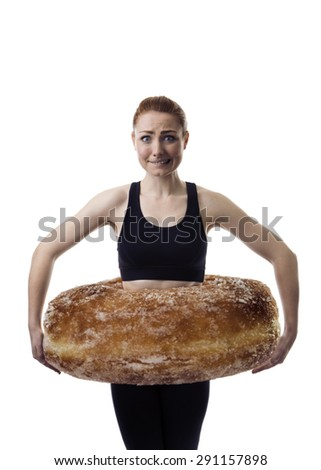 woman with a large donut around her waist like a hula hoop as if she is wearing it and scared to put on weight - stock photo