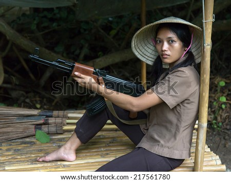 woman with a machine gun sits in a bamboo shelter - stock photo