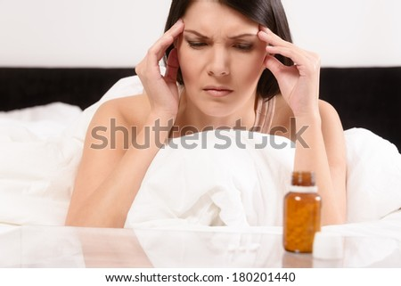 Woman with a migraine headache lying in bed frowning in pain with her hands to her temples contemplating the wisdom of taking a row of tablets laid out on a table in front of her - stock photo