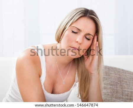 Woman with a migraine sitting holding her throbbing head - stock photo