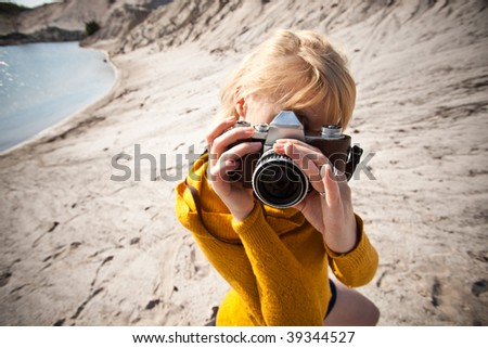 woman with a old camera taking photos in the desert - stock photo