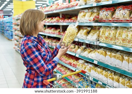 Woman with a package pasta in the shop - stock photo