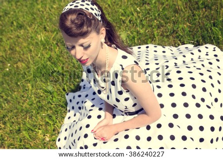 woman with a petticoat dress, a braid and a suicide roll sitting on the meadow, concept style and fashion