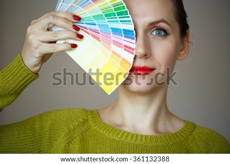 Woman with a red lips looking to a color paint palette