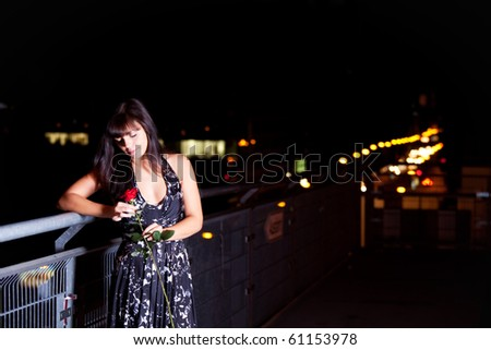 woman with a red rose outdoor in the city