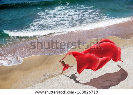 woman with a red tissue on the beach - stock photo