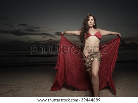 Woman with a red veil on the beach