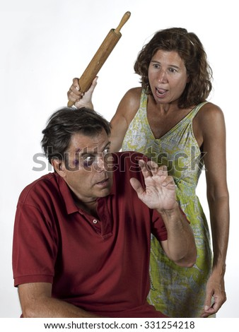 woman with a rolling pin, beating her husband  - stock photo