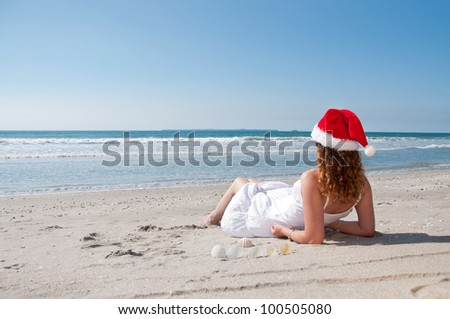 Woman with a santa hat on while vacationing at the beach in the southern hemisphere while vacationing at the beach so she can send image to friends and wish them a merry christmas