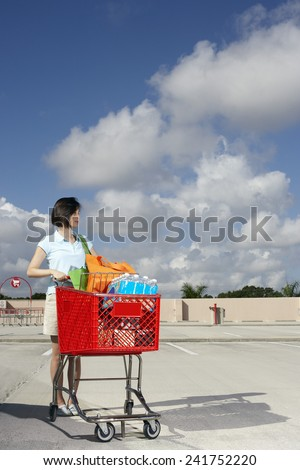 Woman with a Shopping Cart in a Parking Lot - stock photo