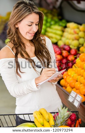 Woman with a shopping list at the local market - stock photo