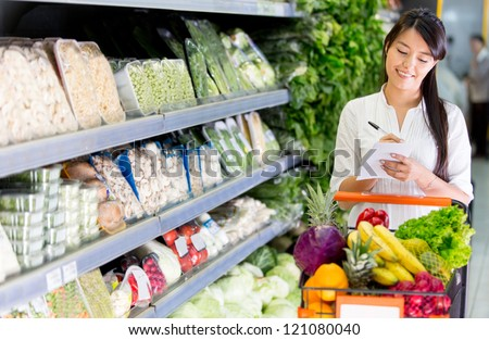 Woman with a shopping list for groceries at the market - stock photo