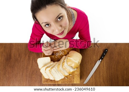 woman with a sliced up loaf of bread layed out on a wooden chopping board taken from a birds eye view from above looking down - stock photo
