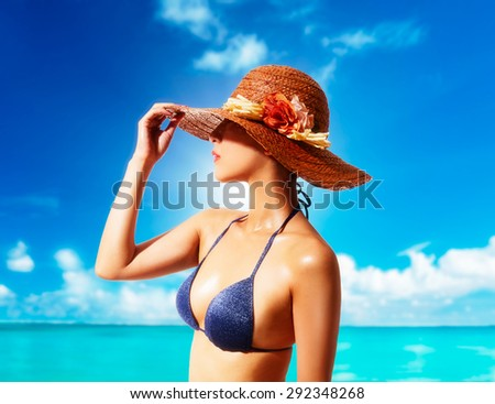 Woman with a straw hat and bikini on the beach. Summer vacation fashion style image.  - stock photo