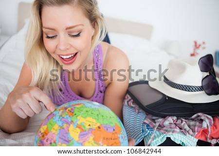 Woman with a suitcase pointing on a globe while lying on her bed - stock photo