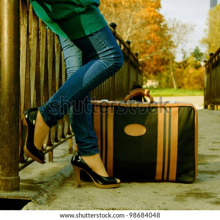 woman with a suitcase standing on the bridge - stock photo
