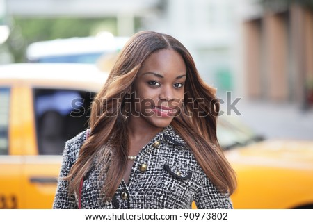 Woman with a taxi cab parked in the background - stock photo