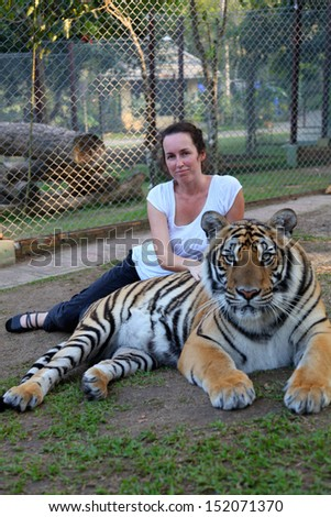 Woman with a tiger in captivity at a zoo. - stock photo