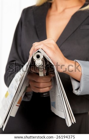 Woman with a weapon hidden under a newspaper - stock photo