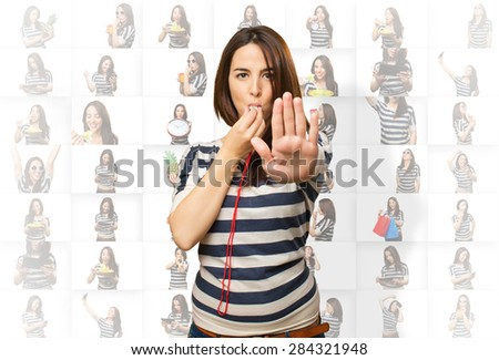 Woman with a whistle doing the stop gesture - stock photo