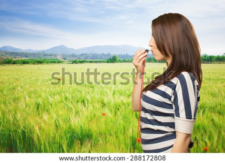 Woman with a whistle. Over meadow background - stock photo