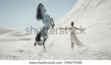 Woman with a white horse on a desert