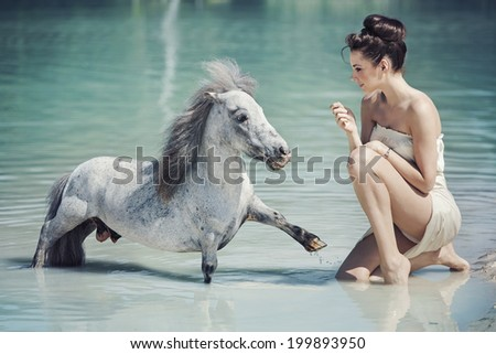 Woman with a white horse on a desert - stock photo