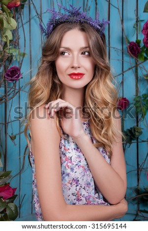 woman with a wreath of flowers on her head. The girl with ornaments in her hair, she is sitting on a swing, her gentle purple dress background is blue. Portrait of a woman with red lips and black eyes - stock photo