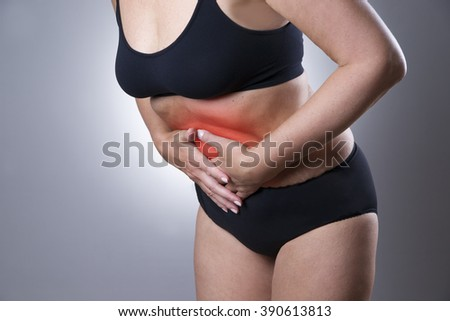Woman with abdominal pain. Ache in human body on a gray background with red dot