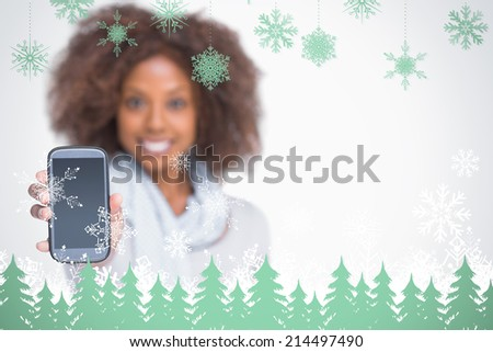 Woman with afro showing her smartphone against snowflakes and fir trees in green - stock photo