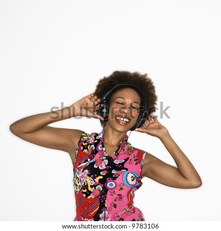 Woman with afro wearing vintage print fabric and listening to headphones smiling and dancing.