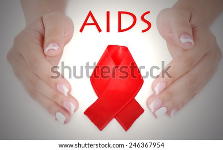 Woman with aids awareness red ribbon in hands - stock photo