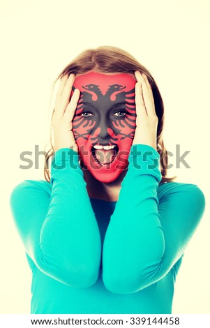 Woman with Albania flag painted on her face. - stock photo