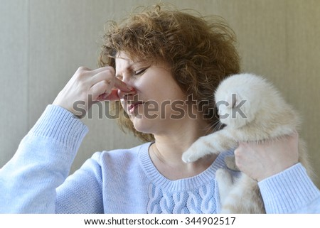 woman with allergy is holding a kitten