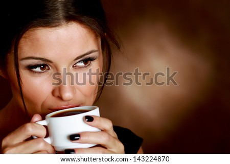 Woman with an aromatic coffee in hands isolated on beige background - stock photo