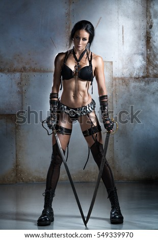 Woman with an athletic physique, in an unusual costume, posing with two swords