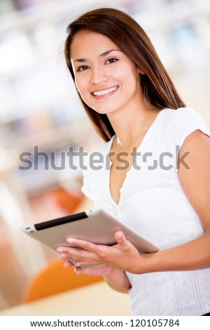 Woman with an e-book reader at the library - stock photo