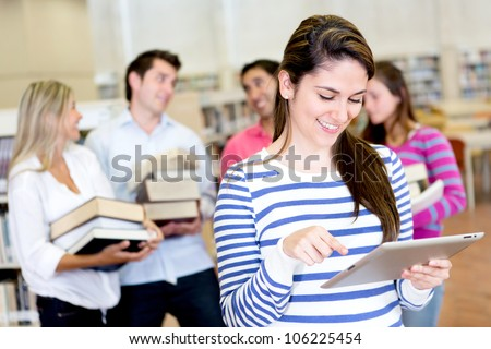 Woman with an e-book reader while friends carry books - stock photo