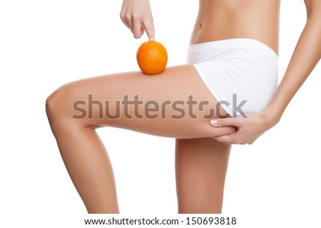 Woman with an orange showing a perfect skin without cellulitis - stock photo