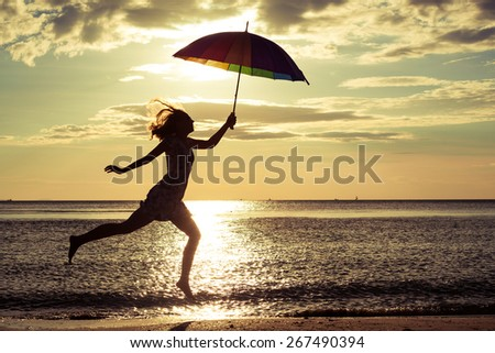 woman with an umbrella jumping on the beach at the sunset time - stock photo